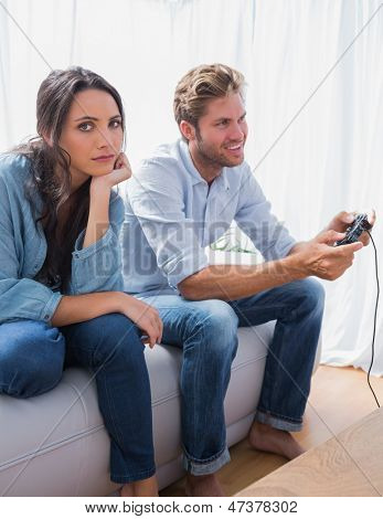 Sad woman annoyed that her partner is playing video games at home on the sofa