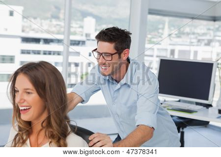 Smiling designers playing on a swivel chair in their office