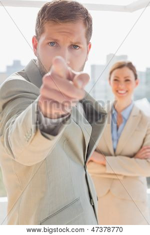 Annoyed businessman pointing at camera with colleague behind him