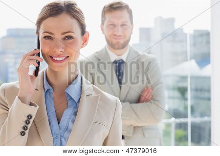 Smiling businesswoman having phone conversation with coworker behind her