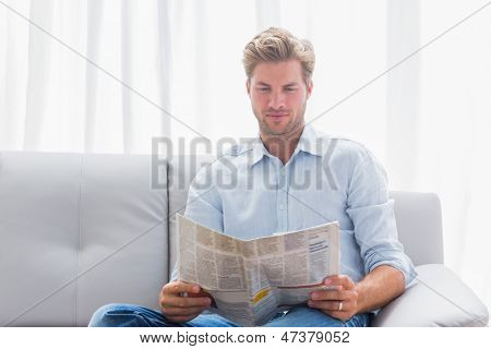 Man reading a newspaper on a couch in the living room