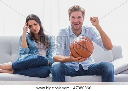 Woman annoyed by her partner watching basketball game in the living room