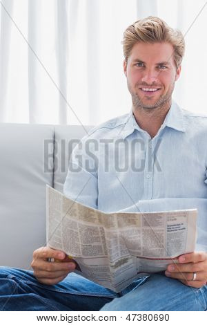 Cheerful man reading a newspaper on a couch in his living room