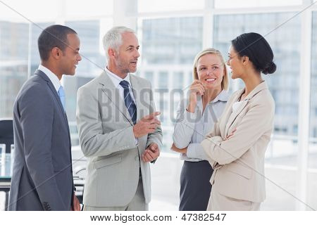 Happy business team talking together in the office