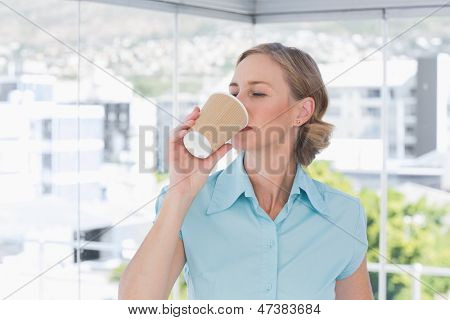 Businesswoman drinking from disposable coffee cup in bright office
