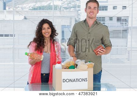 Smiling volunteers taking out food from donations box for a charity