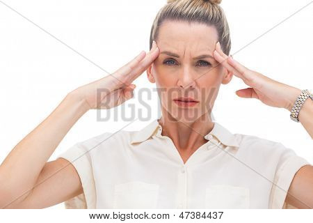 Wincing businesswoman with hand on head looking at the camera