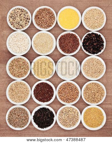 Large grain food selection in white porcelain bowls over papyrus background.