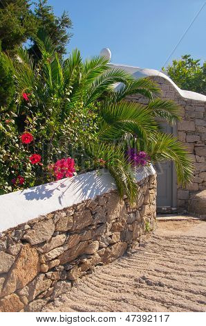Stone Wall With A Gray Door In A Garden With Palm Trees And Flowers.