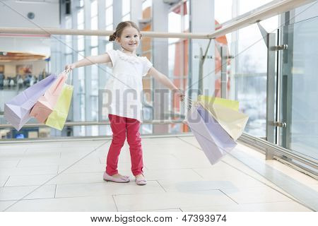 Young girl laden with paper shopping bags