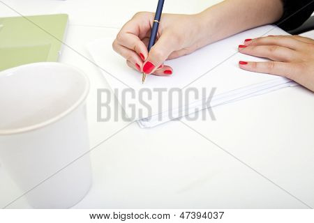 Close up of woman's hands writing on paper.