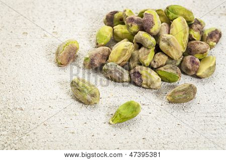 a pile of raw pistachio nuts on a rough white painted barn wood background
