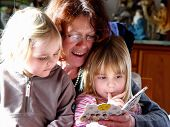 stock photo of niece  - aunt with nieces reading in a picture book - JPG