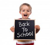Young child holding back to school chalk blackboard sign standing against white background