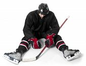 stock photo of disappointed  - Ice hockey player sitting on ice with disappointment - JPG