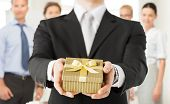 stock photo of proposal  - close up of man hands holding gift box in office - JPG