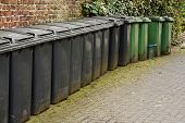 foto of dust-bin  - Horizontal ine of wheelie bins used for the storage of domestic rubbish or household garbage disposal - JPG