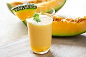 image of cantaloupe  - Cantaloupe smoothie in a glass by fresh cantaloupe - JPG