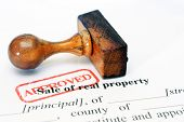 stock photo of deed  - Close up of rubber stamp Sale of real property - JPG