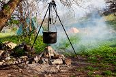 stock photo of saucepan  - Saucepan hanging over the fire on a tripod - JPG