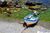 pic of off-shore  - a boat on the shore by the clear blue waters of the  - JPG