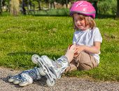 stock photo of unsafe  - Girl with helmet on but without protective knee pads crying - JPG