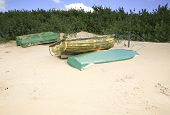 stock photo of dingy  - Three dingies upturned on sand dunes near a river - JPG