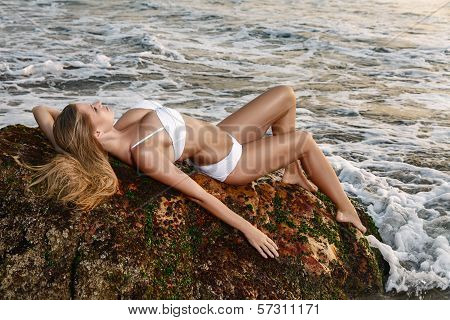 Young Woman Lying Down At Sea