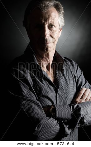Low Key Shot Of A Handsome Senior Man Against Dark Background