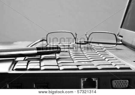 Laptop With Reading Glasses And Pen