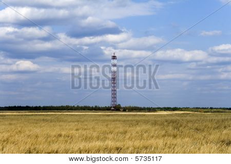 Communications Tower On Field With Cloudy Sky Background