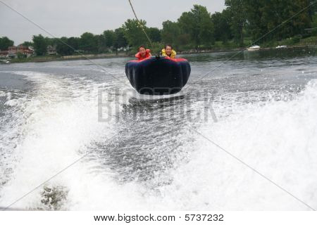 A family on a water tube sailing in the air