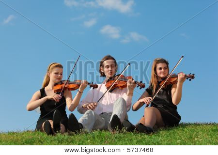 Three Violinists Sit And Play On Grass Against Sky