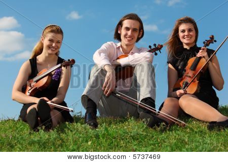 Three Violinists Sit On Grass Against Sky