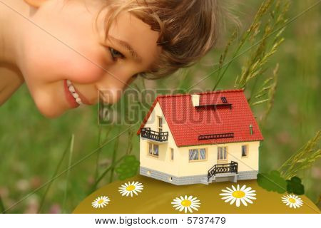 Child Looks On Model Of House Outdoor