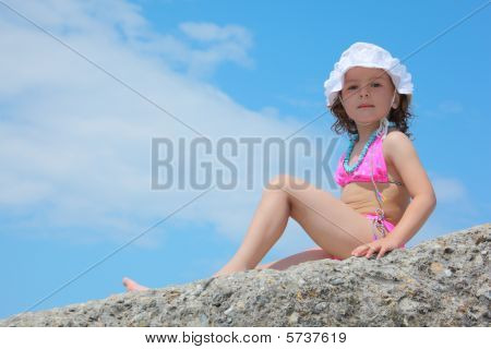 Little Girl Sits On Rock Against Sky