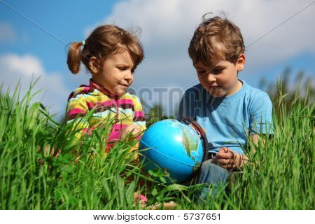 Girl And Boy With Globe On Meadow