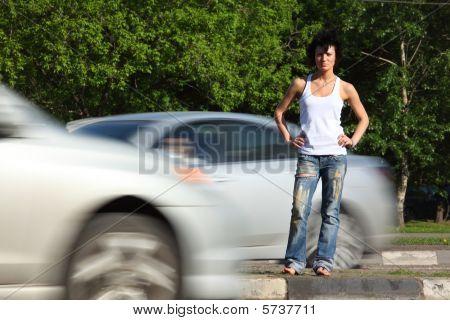 Mädchen steht auf Straße unter Autos