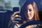 stock photo of ban  - Close up of a front view of a woman driving a car and typing on a smart phone - JPG