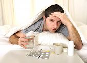 image of alcohol abuse  - exhausted young Man in bed with coffee water and tablets suffering hangover and headache - JPG