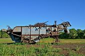 picture of threshing  - An old threshing machine stands in the pasture with extra parts stored on the top - JPG