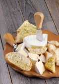 pic of brie cheese  - Arrangement of Delicious Camembert Brie and Parmesan Cheese with Garlic and Herbs Bread and Cheese Knifes on Cheese Board closeup on Rustic Wood background - JPG