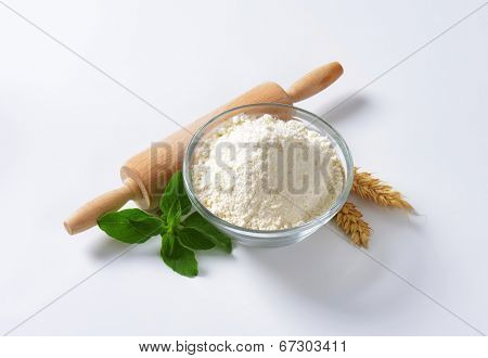 white flour in the glass bowl with rolling pin and wheat ear