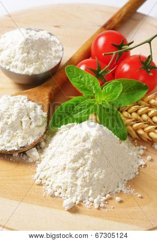 small piles of soft wheat flour, wooden spoon and tomatoes with wheat ear in a detail