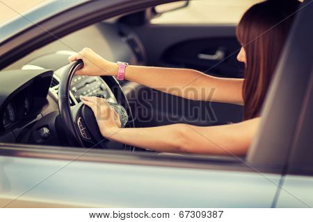 transportation and vehicle concept - woman driving a car with hand on horn button