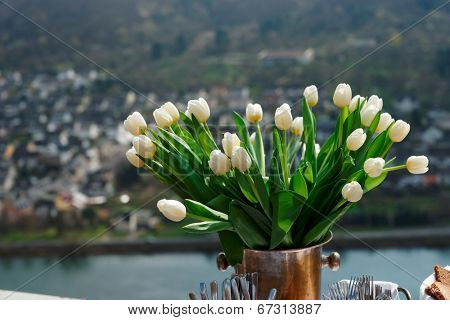 Bunch of tulips on table, river and village in the background