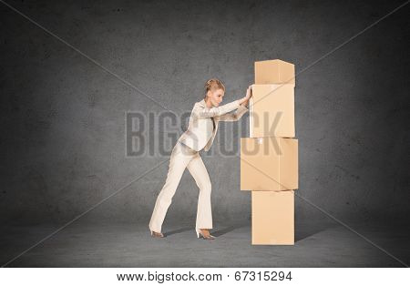 business, postal and office concept - businesswoman pushing tower of cardboard boxes