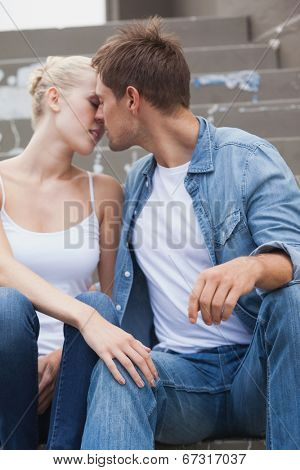 Hip young couple in denim sitting on steps about to kiss on a sunny day in the city