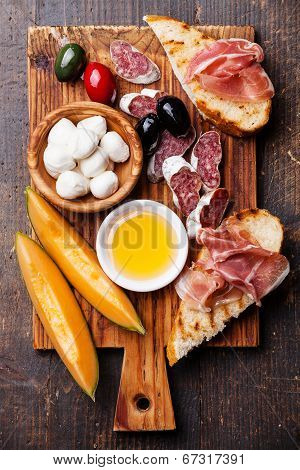 Prosciutto Ham, Slices Of Melon Cantaloupe, Mozzarella Cheese And Olives On Cutting Board