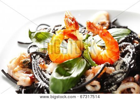 Black spaghetti with seafood isolated on white background